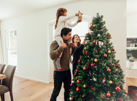 Photo pour Family decorating a Christmas tree. Young man with his daughter on his shoulders helping her decorate the Christmas tree. - image libre de droit