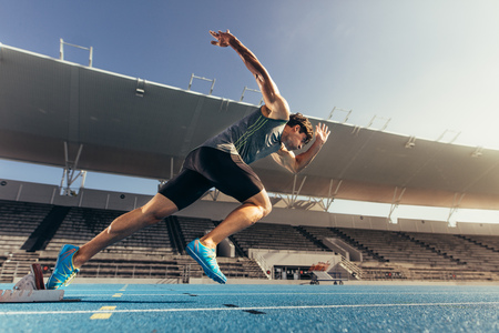 Photo pour Runner using starting block to start his run on running track in a stadium. Athlete starting his sprint on an all-weather running track. - image libre de droit