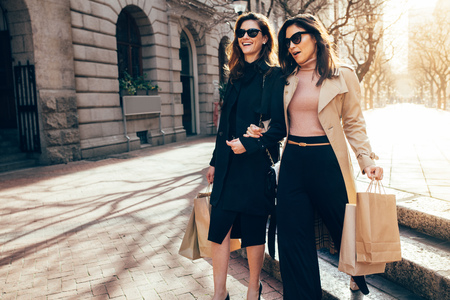 Photo pour Stylish women friends walking on the city street with shopping bags. Female shoppers carrying shopping bags while walking along the road. - image libre de droit