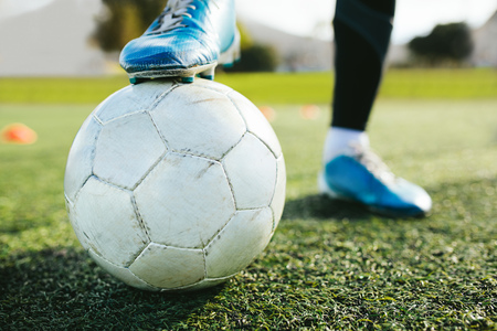 Foto de Close up of teenager's legs with a ball on football pitch. Cropped shot of soccer player training on the artificial grass field. - Imagen libre de derechos