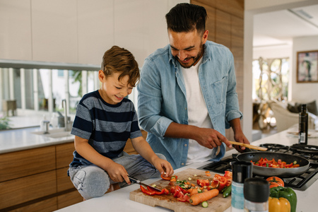 Foto de Little boy cutting vegetables while his father cooking food in kitchen. Father and son preparing food at home kitchen. - Imagen libre de derechos