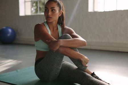 Foto de Woman resting in between workouts. Healthy young female taking rest after training in gym. - Imagen libre de derechos