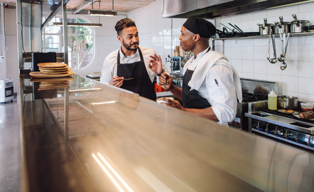 Two male cooks wearing uniform working in commercial kitchen. Professional chefs discussing the taste of new dish they cooked together in restaurant kitchen.