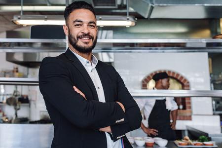 Foto de Portrait of young businessman standing in his restaurant with staff in kitchen. Proud restaurant owner standing with his arms crossed and looking at camera. - Imagen libre de derechos