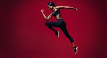 Sports woman running over red background. Full length shot of healthy young african woman sprinting.