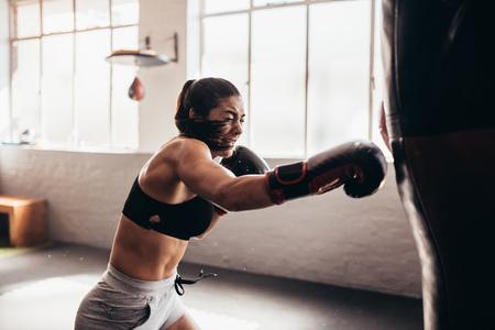 Foto de Female boxer hitting a huge punching bag at a boxing studio. Woman boxer training hard. - Imagen libre de derechos