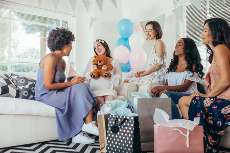 Pregnant woman celebrating baby shower party with friends. Pregnant woman receiving gifts from friends.