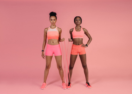 Foto de Two women doing exercises with resistance band over pink background. Fitness females working out with resistance band. - Imagen libre de derechos