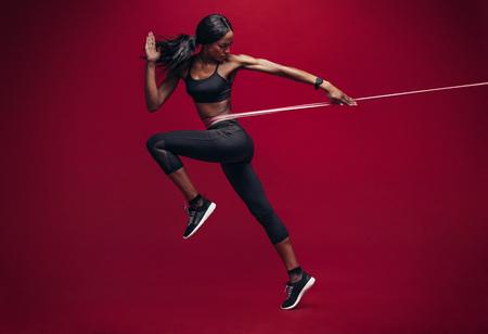 Sporty woman exercising with resistance band on red background. African female athlete working out with elastic bands in studio.