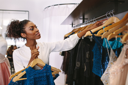 Photo for Fashion designer having a look at designer dresses in her fashion studio. Customer selecting dresses in a fashion clothes shop. - Royalty Free Image