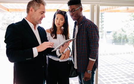 Foto de showing terms of contract on tablet to interracial couple. Real estate agent sharing property details with clients. - Imagen libre de derechos