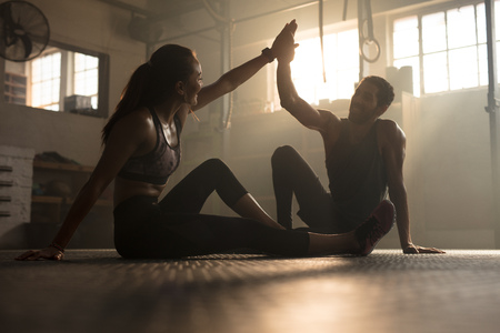 Foto de Healthy man and woman sitting on floor and giving each other high five at the gym. Fitness people after successful exercising session in gym. - Imagen libre de derechos