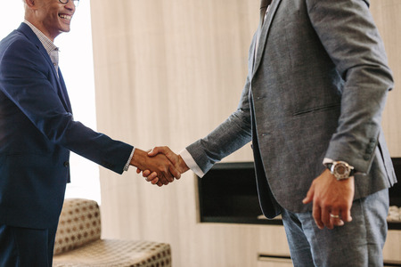 Two business persons shaking hands after an agreement. Close up of business people hand shake in office.
