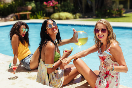 Photo pour Diverse group of female friends sitting by the resort swimming pool having cocktails and smiling. Women having a poolside party on a summer day. - image libre de droit