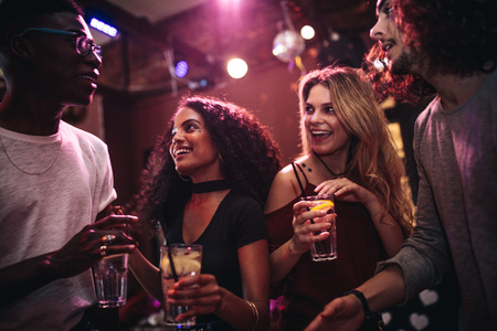 Foto de Diverse group of young people with drinks in a club. Happy men and women enjoying nightout at bar. - Imagen libre de derechos