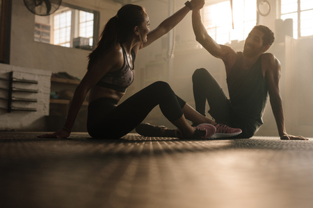 Fit man and woman sitting on floor and high fiving at the gym. Fitness couple after successful workout session in gym.