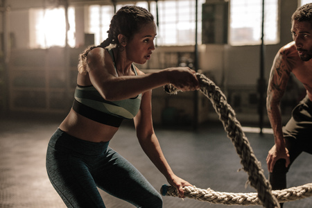 Photo pour Female exercising with battle ropes at the gym with coach. Athlete doing battle rope workout at gym with trainer. - image libre de droit