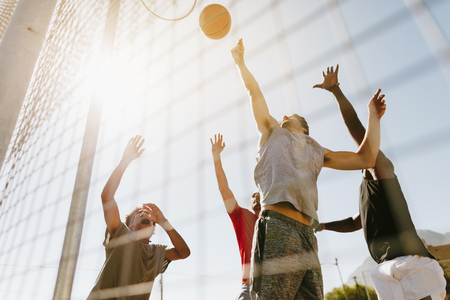 Foto de Four men playing basketball in a basketball court on a sunny day. Men jumping high to reach for the ball near the basket. - Imagen libre de derechos