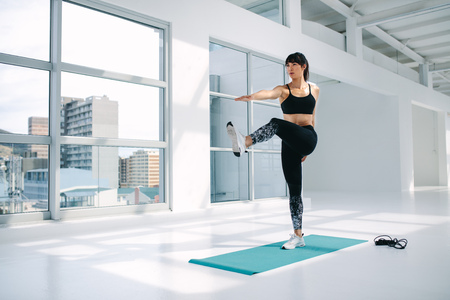 Foto de Full length of a young healthy woman doing stretching exercise on the mat at gym. Female in sportswear standing on one leg and touching the toe of the outstretched leg with hand. Standing big toe hold pose - Utthita Hasta Padangusthasana. - Imagen libre de derechos