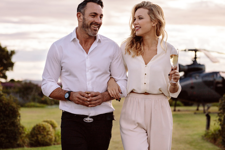 Photo pour Couple with a glass of wine walking outdoors with a helicopter in background. Man and woman with a drink walking together. - image libre de droit