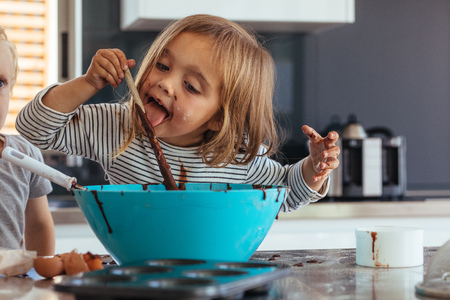 Foto de Little girl licking spoon while mixing batter for baking in kitchen  and her brother standing by. Cute little children making batter for baking. - Imagen libre de derechos