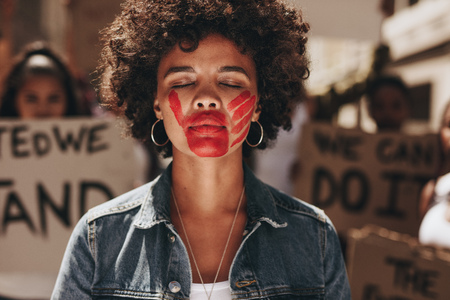 Woman with a hand print on her mouth, demonstrating violence on women. Woman protesting against domestic violence with group in background.