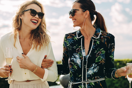 Beautiful women walking and talking outdoors. Best friends having a great time together.