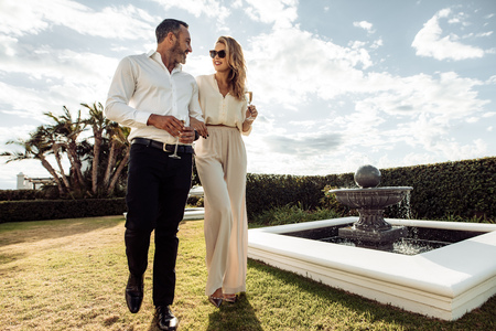 Foto de Stylish couple walking outdoors in lawn with a glass of wine. Man and woman looking at each other and walking together outdoors.. - Imagen libre de derechos