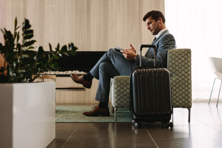 Photo pour Businessman reading a magazine while waiting for his flight at airline terminal lounge. Entrepreneur at airport waiting area reading a magazine. - image libre de droit