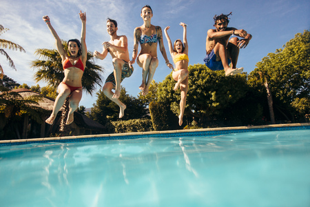 Foto de Happy young friends jumping into outdoor swimming pool and having fun. Group of men and women jumping into a holiday resort pool. - Imagen libre de derechos