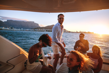 Photo pour Happy friends drinking and having fun in boat party. Young rich people enjoying sunset boat party. - image libre de droit