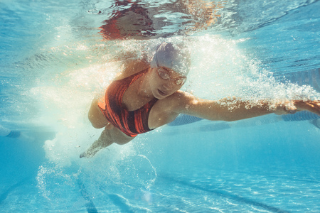 Foto de Underwater shot of woman swimming the front crawl in sports pool. Fit female athlete practising in swimming pool. - Imagen libre de derechos