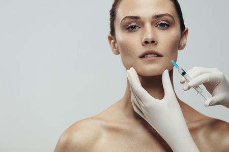 Photo pour Portrait of young woman getting cosmetic injection. Close up of beautiful woman gets injection in her face against grey background with copy space. - image libre de droit