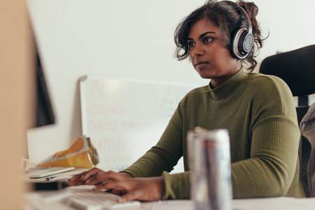 Photo for Female programmer working in a software developing company office. Woman wearing headphones coding on desktop computer. - Royalty Free Image