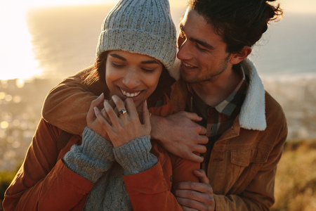 Foto de Close up portrait of affectionate young couple on winter holiday. Handsome young man embracing his girlfriend from behind in a winter day. - Imagen libre de derechos