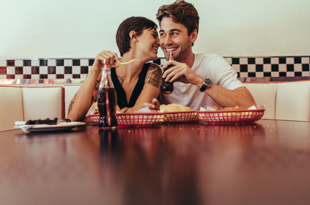 Photo pour Smiling woman sitting close beside her partner at a restaurant and eating food. Romantic couple sitting in a diner with food and soft drinks on the table. - image libre de droit