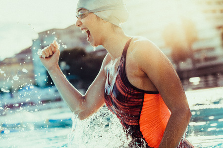 Foto de Excited female swimmer with clenched fist celebrating victory in the swimming pool. Woman swimmer cheering success in pool wearing swim goggles and cap. - Imagen libre de derechos