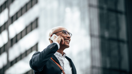 Photo pour Man in formal clothes wearing office bag walking on street while talking on mobile phone. Smiling businessman talking over cell phone while commuting to office with a glass facade building in background. - image libre de droit