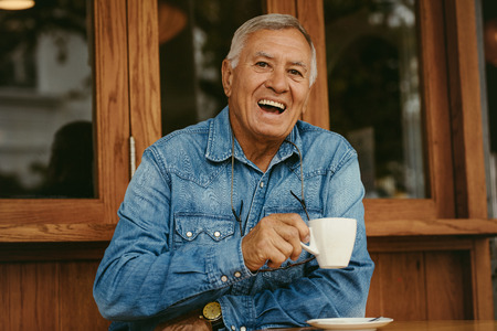 Foto de Portrait of cheerful senior man having coffee at cafe. Smiling old man relaxing at cafe. - Imagen libre de derechos