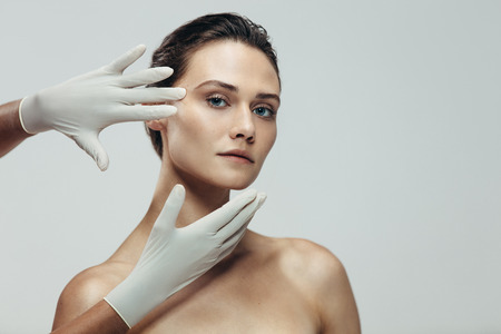 Foto de Beautician hands with gloves touching beautiful woman face before plastic surgery. Female standing against grey background with a cosmetologist touching her face. - Imagen libre de derechos