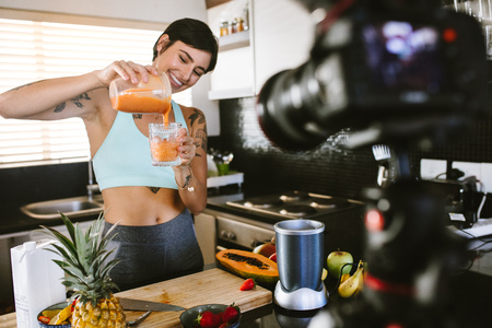 Foto de Woman pouring fresh smoothie into a glass from a juicer. Food blogger recording a vlog on camera on fresh and healthy smoothie. - Imagen libre de derechos