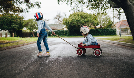 Photo pour Little girl wearing helmet pulling her sister sitting in a wagon cart on the road. Kids playing outdoors with toy trolley. - image libre de droit