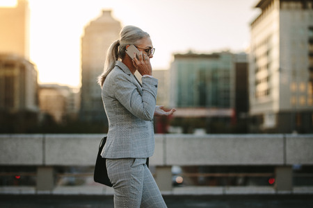 Foto de Side view of mature woman in business suit walking back to home talking on phone. Senior businesswoman using cellphone on city street with urban background. - Imagen libre de derechos
