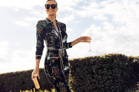 Foto de Stylish young woman walking with glass of wine. Wealthy female with wine walking outdoors. - Imagen libre de derechos