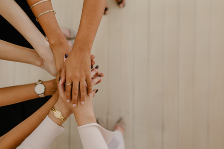 Photo pour Top view of business people putting their hands together. Stack of hands with lots of copy space. Unity and teamwork concept. - image libre de droit