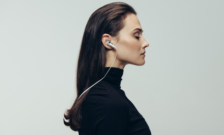 Photo for Side view of woman in black dress wearing earphones with eyes closed. Woman wearing earphones against grey background. - Royalty Free Image