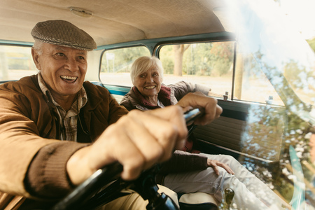 Photo pour Smiling senior man driving a old car with a woman sitting next to him in passenger seat. Happy senior couple going on a road trip. - image libre de droit