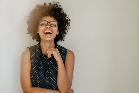 Foto de Portrait of excited young woman standing by a wall and laughing. Cheerful young african female with curly hair and spectacles. - Imagen libre de derechos