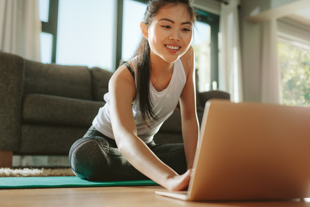 Foto de Woman using laptop while exercising at home. Female in sportswear sitting on floor and watching exercise video for her workout. - Imagen libre de derechos