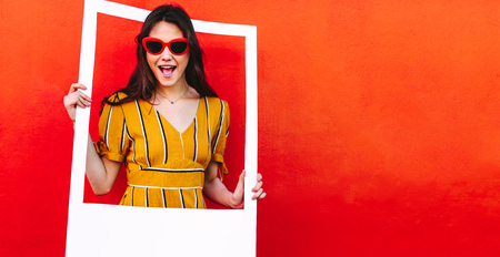 Photo for Excited girl standing against red wall holding a empty picture frame. Beautiful woman in sunglasses looking through blank photo frame. - Royalty Free Image